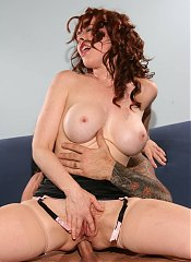 Mature redhead Mae Victoria sucking off a cock before she lets it slide inside her ass